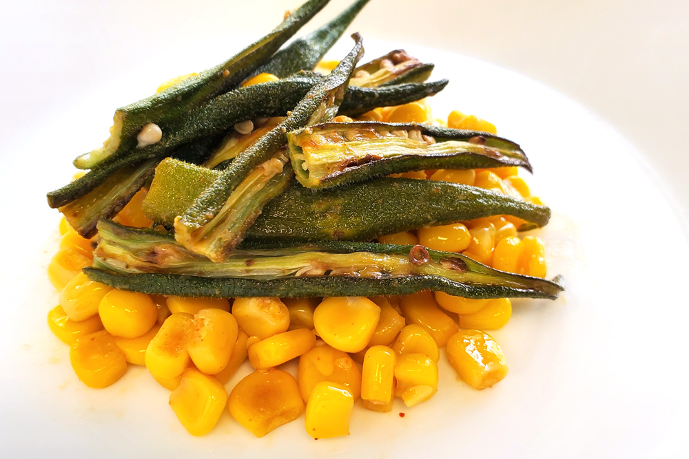 cooked corn topped with okra sliced length-wise on a white plate
