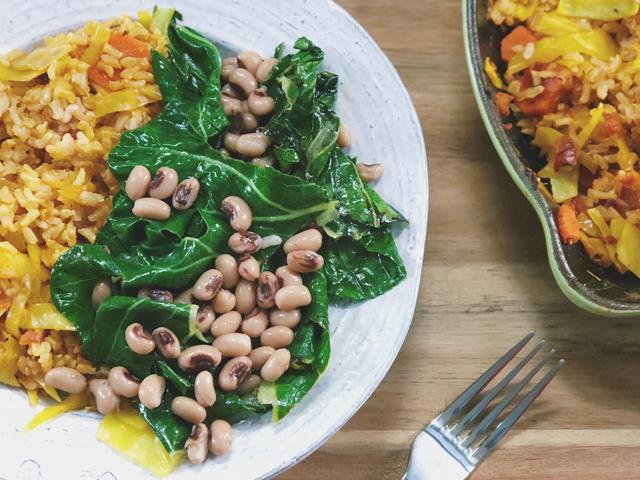 white bowl of rice with cooked carrots, cabbaged mixed in and greens with black-eyed peas