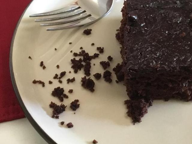 serving of chocolate cake on white plate with red placemat in background