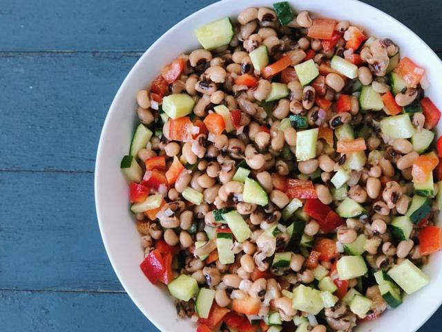 bowl of black eyed peas with vegetables on a blue background