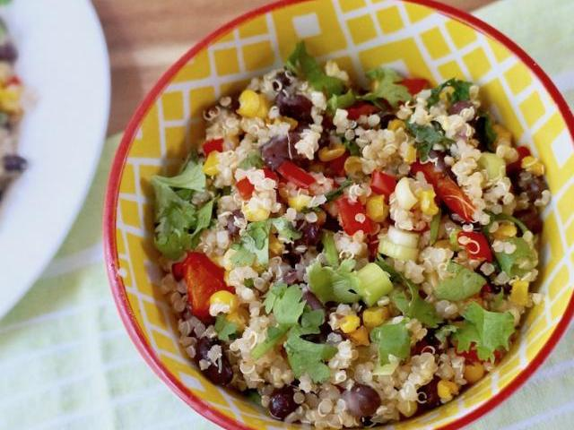 bowl of cooked quinoa with black beans, red peppers, and corn topped with cilantro