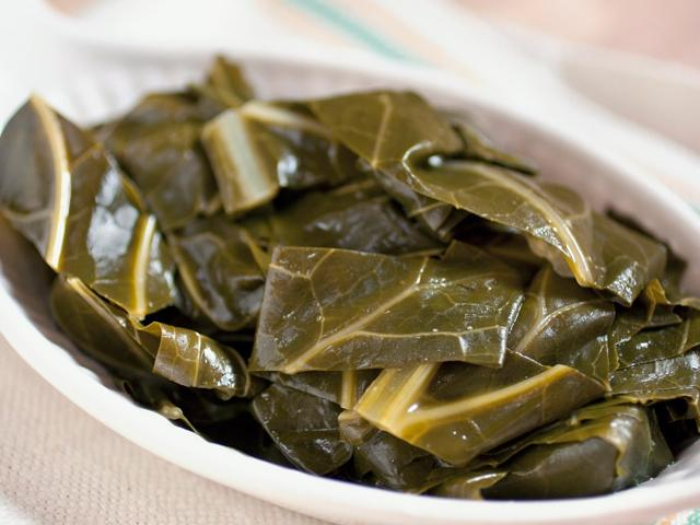 bowl of cooked collard greens on a striped towel