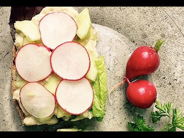 sliced radish, hummus, cucumbers and lettuce on whole grain bread on a clear plate