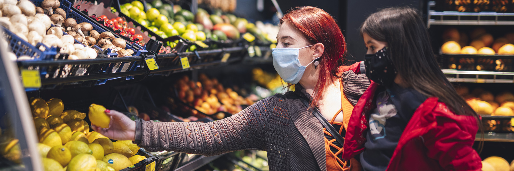 woman and daughter shopping for produce wearing masks
